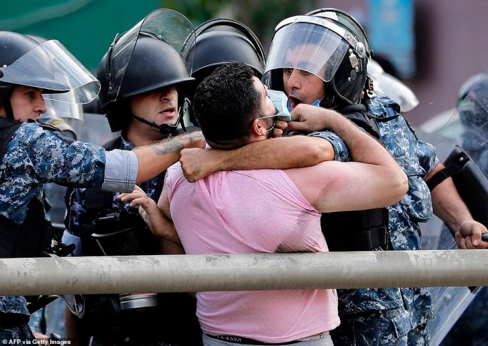 Police confront a protester during clashes outside the French ambassador's residence in Beirut on Friday