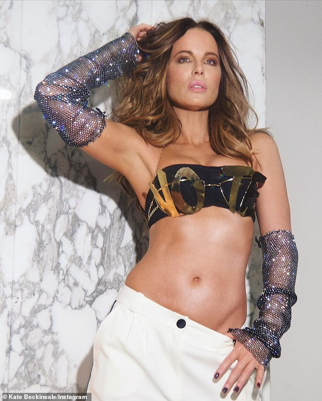 Strike a pose: Kate also encouraged fans to vote as she posed in the custom gold 'VOTE' bra in a series of snaps on Friday