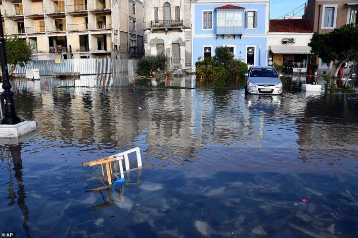 A car is barely above water while a chair is partly submerged in a road in Vathi today after high waters brought by the quake