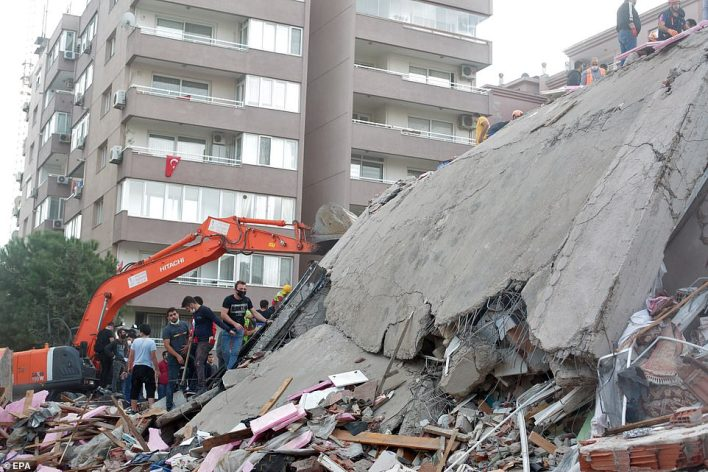 Rescue workers sift through the rubble of  building in Izmir, Turkey, after an earthquake that killed at least twelve