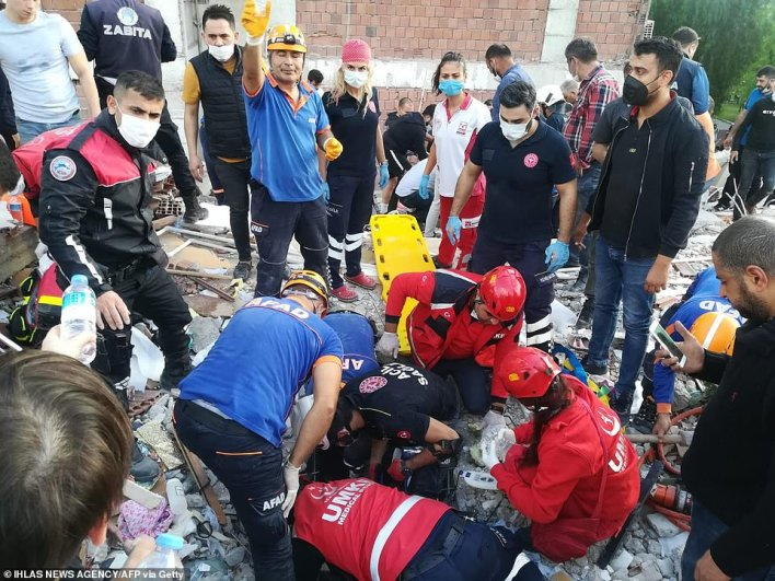 Rescuers search for survivors at a collapsed building after a powerful earthquake struck Turkey's western coast