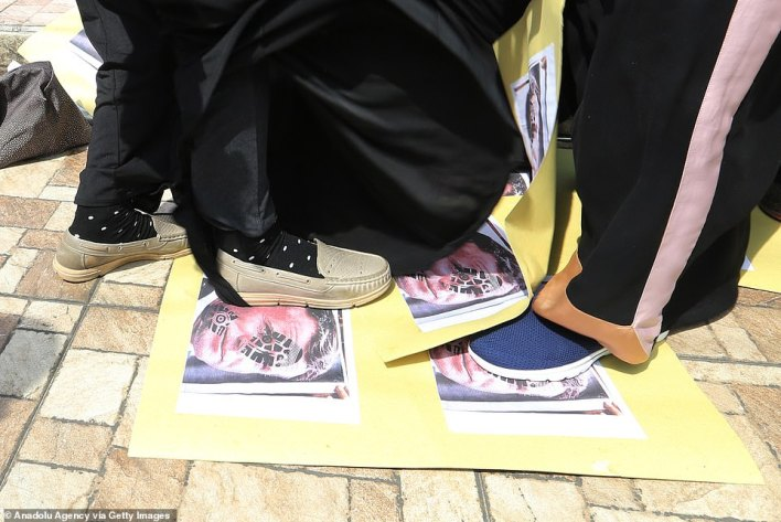 INDONESIA: People stand on Macron portraits defaced with footprints in Medan in Indonesia's North Sumatra province - in the country with the world's largest Muslim population