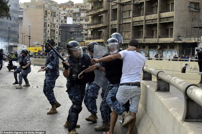 Lebanese riot police hit a protester during a protest outside the Pine Palace, which is the residence of the French ambassador, in Beirut