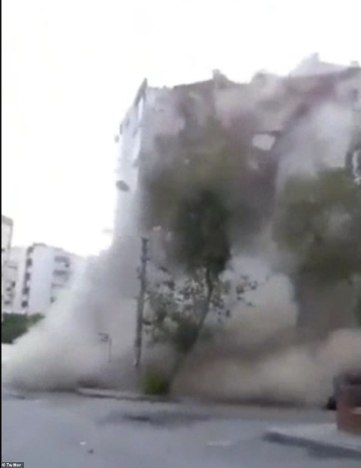 The air is filled with dust as the seven- story building collapses within moments