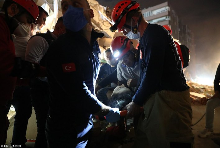 The moment a rescue team carry an injured woman out of the debris in Izmir, Turkey