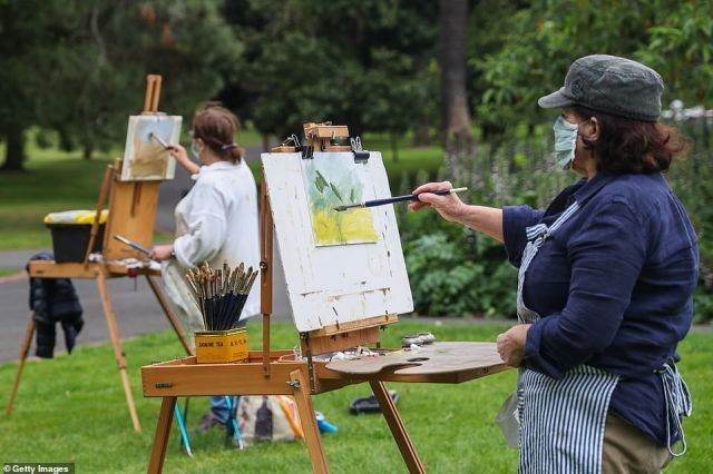 A group of artists are seen wearing masks are seen painting outdoors at Treasury gardens on Saturday
