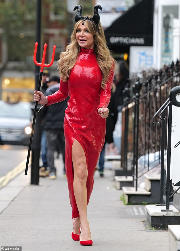 Stunning: Lizzie added height to her frame with seven #-inch red stilettos and she clutched a devil trident