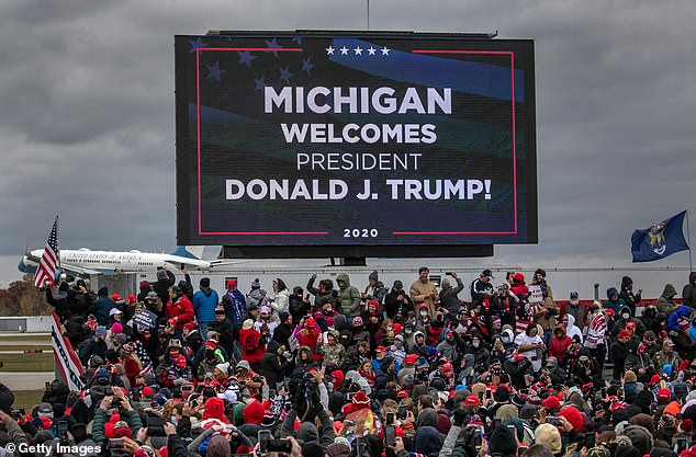 Supporters of U.S. President Donald Trump cheer as Air Force One arrives to a campaign rally at Oakland County International Airport on Friday in Waterford Township, Michigan