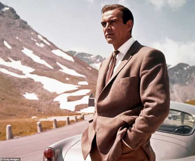 Sean Connery poses as James Bond next to his Aston Martin DB5 in a scene from the United Artists film 'Goldfinger' in 1964