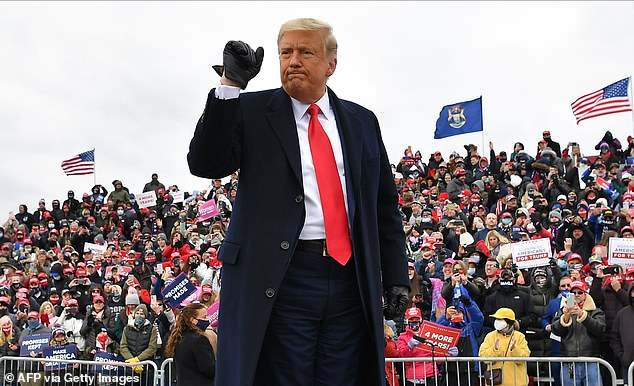 """US President Donald Trump gestures onstage at a """"Make America Great Again"""" rally at Oakland County International Airport, on October 30, 2020, in Waterford Township, Michigan"""