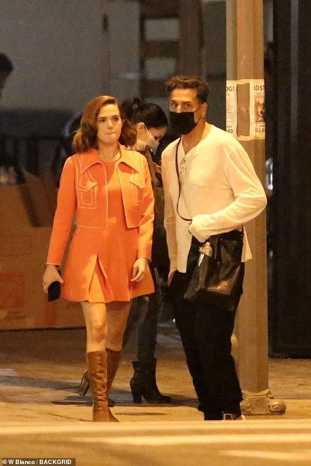 Sixties chic: Zoey was later spotted working an orange, sixties-styled dress with pleated skirt and knee-high boots