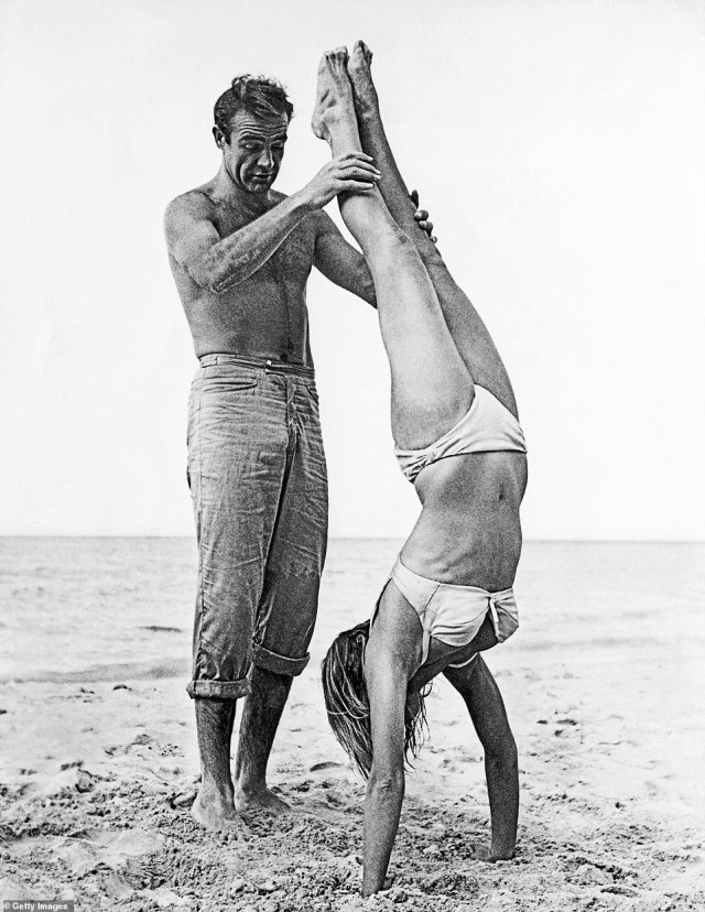 Sean Connery holds Swiss actor Ursula Andress while she does a handstand on a beach in a white bikini on the set of the film, 'Dr. No'