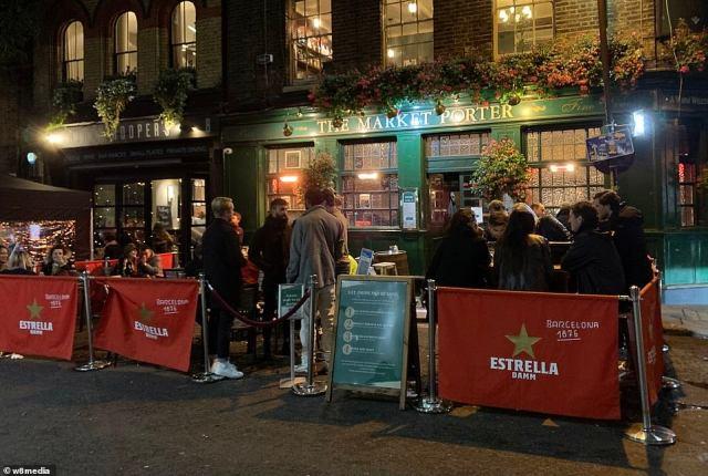 People gather outside the Market Porter pub in Borough Market, Southwark ahead of England's new shutdown