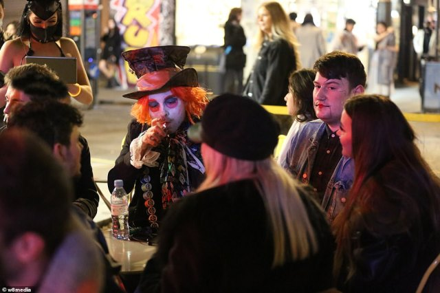 Revellers including a man dressed as the Mad Hatter from Alice in Wonderland enjoying a night out in Soho