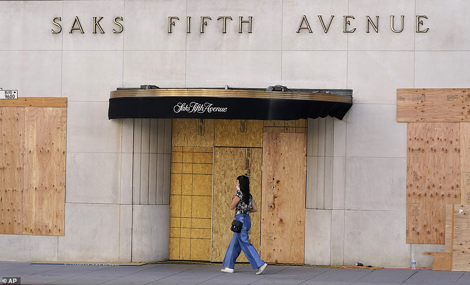 A pedestrian passes a boarded up entrance at the Saks Fifth Avenue store Friday in Beverly Hills