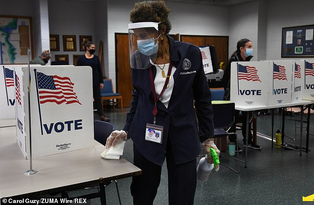 A poll worker in Alexandria sanitizes the voting station on Saturday
