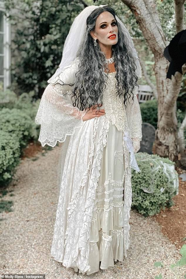 Bridal spooky: The 47-year-old looked ravishing in a floor-length Victorian style wedding dress, trimmed in off-white lace and ruffles