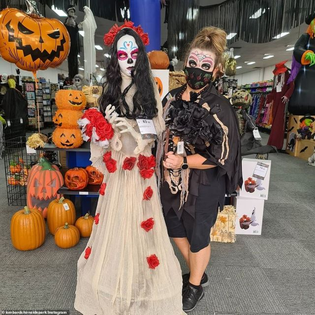 A woman sporting a skeleton costume and decorative make up poses for a photo alongside a Day of the Dead mannequin