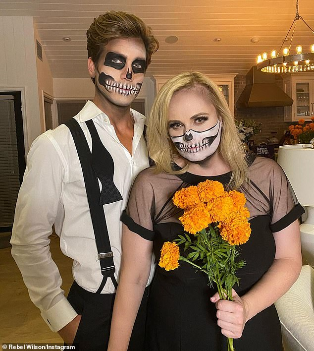 Ghostly greetings! Rebel Wilson (pictured with boyfriend Jacob Busch), 40, showed off her incredible 20 KILO weight loss in a semi-sheer black dress, as she joined other Aussie stars including Shanina Shaik and Ruby Rose in celebrating Halloween this weekend on Instagram