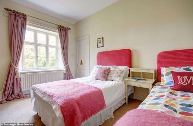 It adds: 'Adjacent to the Royal Fruit Farm, this property has beautiful views across the Norfolk countryside. This large family home provides six bedrooms and three attic rooms.' Pictured, one of the bedrooms available in the manor house