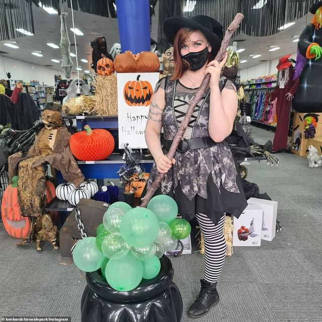 A witch in black and white stripped stockings stirs a cauldron filled with green balloons inside a costume store in Melbourne