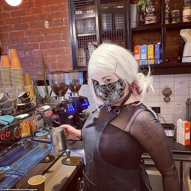 A Victorian barista dressed as a spooky witch while making coffees for customers on Saturday with a cobb-web print face mask