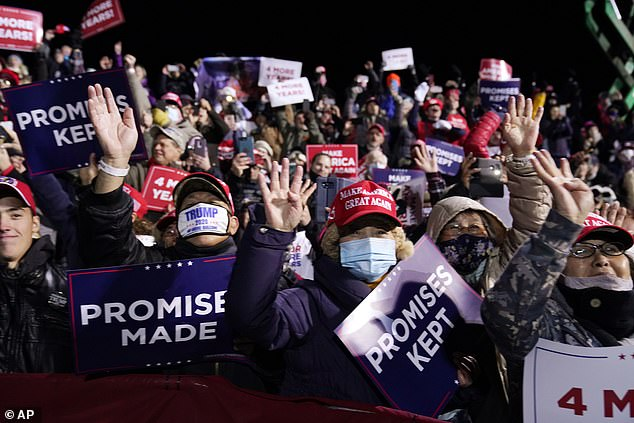 MAGA fans pictured during the rally raising their hands and holding up four fingers as they chant 'Four More Years'