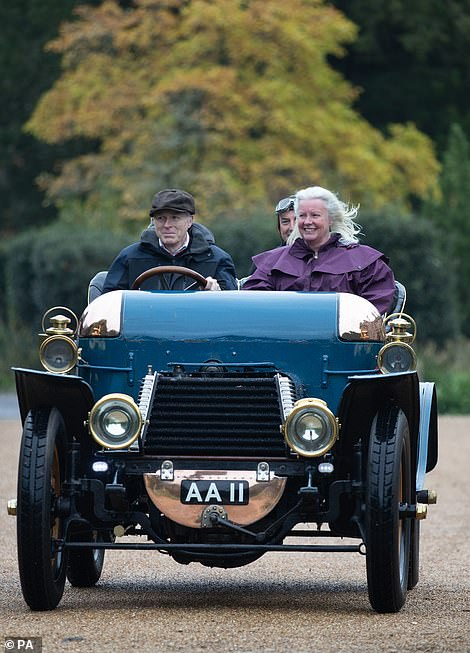 Lord Montagu (left) drives a 1903 Daimler into the grounds of Beaulieu House in the New Forest