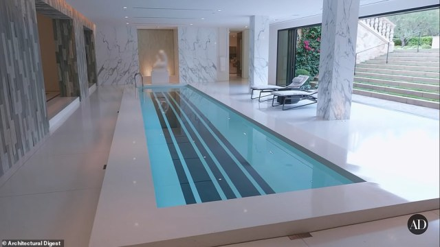 Located at 330 S. Mapleton Drive, the lavish mansion offers a life of luxury and Hollywood glamour across its 31,624-square-feet to future residents. A view of the indoor pool with sliding doors that open up to the outside above