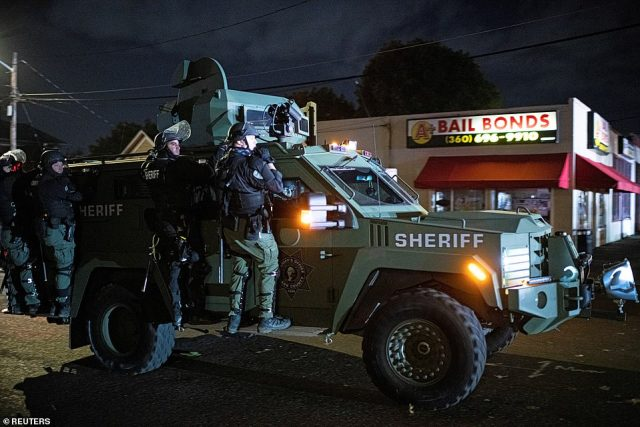 Law enforcement officers ride on an armored vehicle during a march by protesters on Saturday