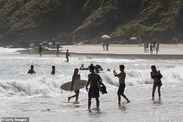 Queensland will review its border rules later this month (Image: Swimmers enter the water at Wategos Beach)