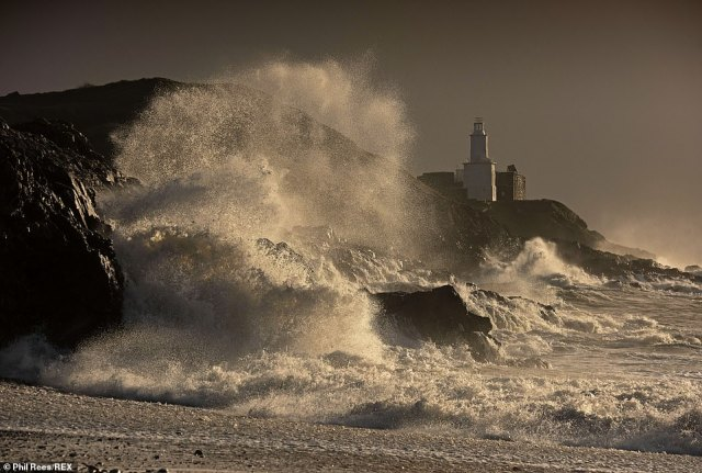 Cold air from Greenland is also set to send temperatures plunging by 10C (50F) ahead of Bonfire Night on Thursday. Pictured:Huge waves smash into the rocks in front of the Mumbles Lighthouse at Bracelet Bay in Swansea, Wales, on Monday