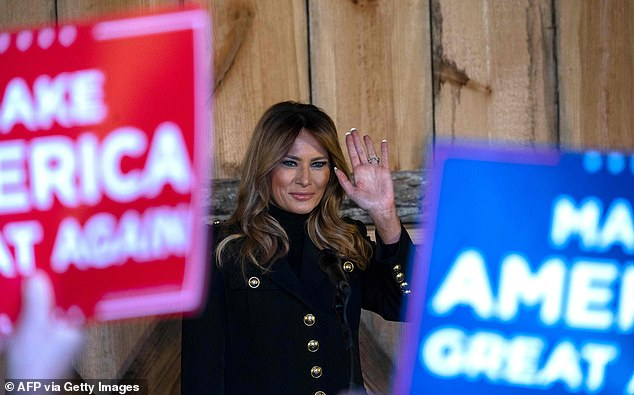 Keeping warm: The First Lady bundled up against the Midwest autumnal chill in a long, dark coat with gold buttons