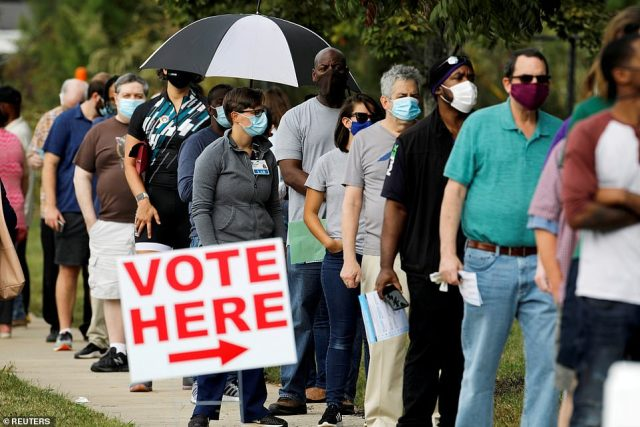 Voters are pictured standing in line to cast their votes in North Carolina on October 15