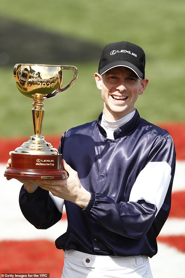 Jye McNeil holds the Melbourne Cup after winning on board Twilight Payment on Tuesday afternoon