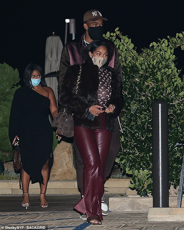 Dressed to impress: Karl-Anthony matched his girlfriend as he rocked a maroon silk bomber jacket a pair of tracksuit bottoms for their outing, while also sporting a New York Yankees cap