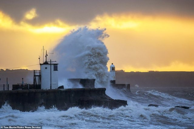 Britain is braced for more downpours today after a fortnight's rain fell in 24 hours during Storm Aiden. Pictured:Huge Waves hit the sea front by the lighthouse at sunrise in Porthcawl, South Wales, on Monday