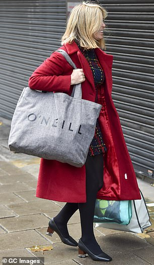 Busy day: The television host certainly had her hands full as she lugged a collection of shopper bags into the studios