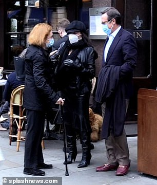 Stylish: Joan wrapped up warm in a sleek black coat and boosted her height in a pair of stylish knee-high boots
