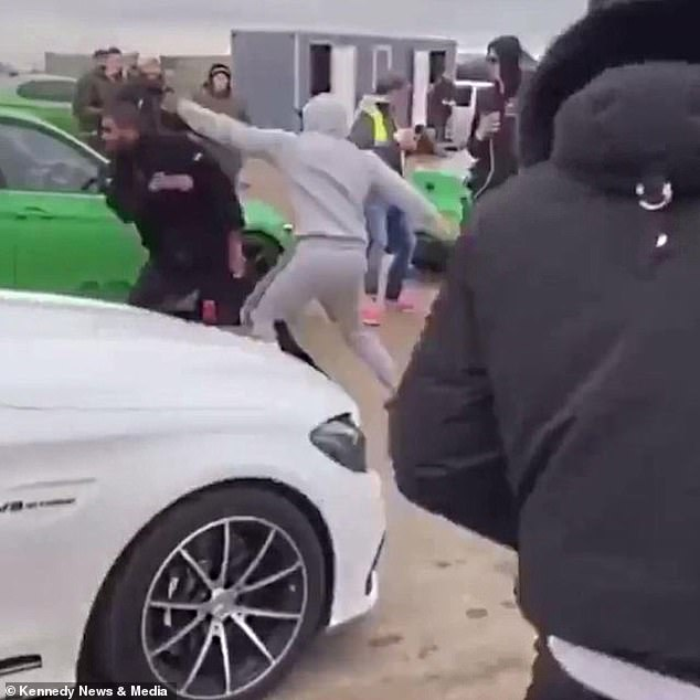 Shocking footage from the event - which sees sports car owners try to reach top speeds in their vehicles - shows a group of men arguing before throwing punches