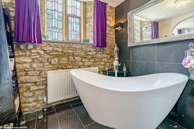 Pictured: Stunning exposed brick walls inside one of the property's bathrooms, which features a freestanding bathtub