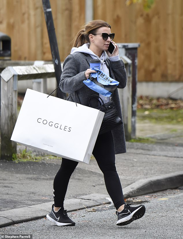 Sportswear: Coleen teamed the look with a grey coat, black trainers and a crocodile print cross-body bag and chatted away on the phone