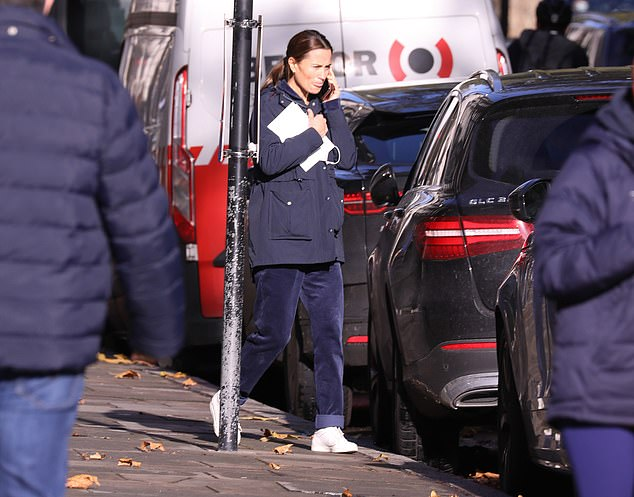 Pippa could be seen holding her mobile in one hand, and a large white envelope in the other as she strolled up the street