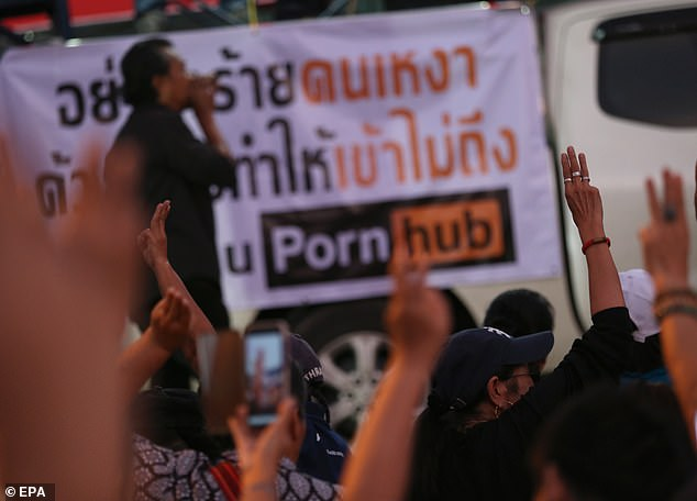 Thai protesters flash the three-finger salute in front of a banner reading 'Don't hurt the lonely person, with inaccessibility and reclaim of Pornhub [sic]' during a protest following the blocking the access of the adult website Pornhub, outside the Ministry of Digital Economy and Society in Bangkok, Thailand today
