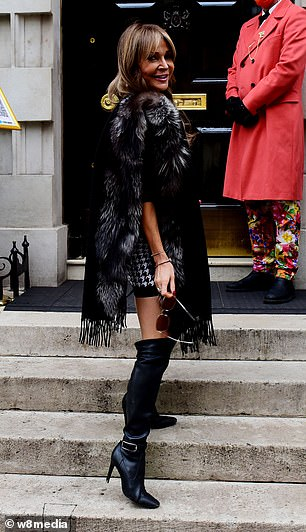 Pose: Styling her brunette tresses into voluminous waves, Lizzie accessorised with a blackhandbag