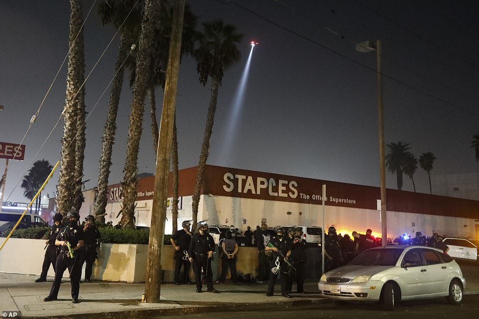 LOS ANGELES: LAPD officers stand guard outside a Staples superstore in LA as authorities declare an unlawful assembly