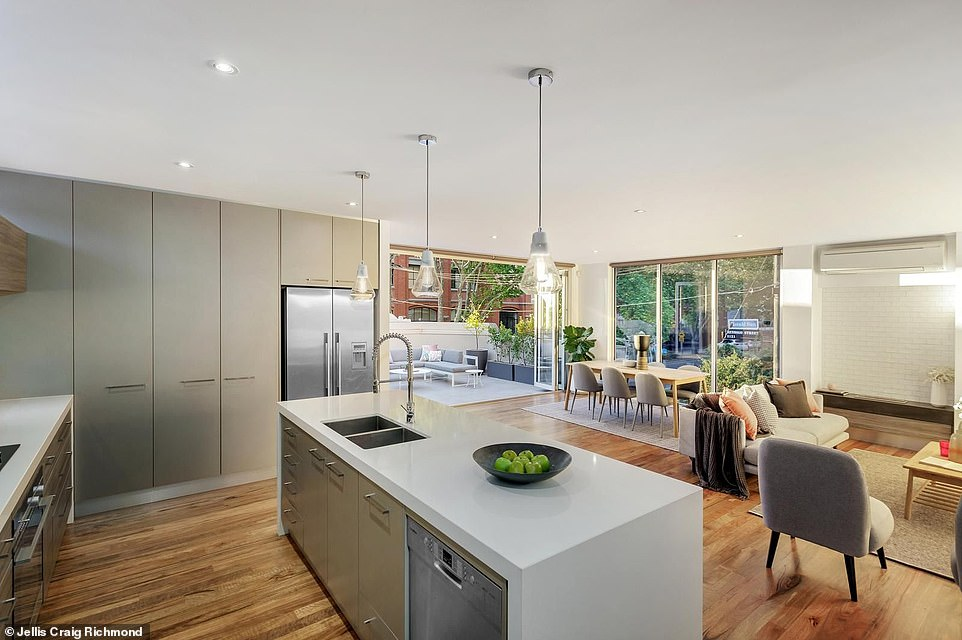 A stunning gourmet kitchen sparkles inside the home with an island bench top and top of the range quality appliances