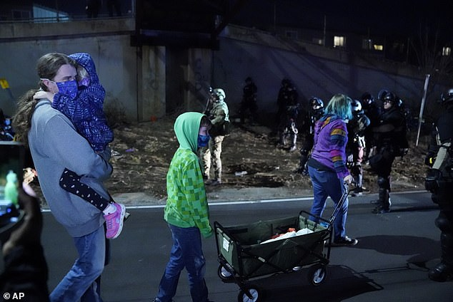 People with children are let through the police line on I-94 during the National Day of Protest rally and march in Minneapolis