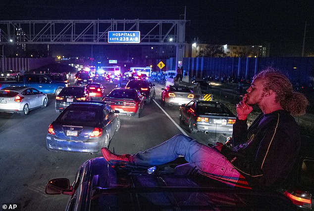 Payton Wood, 21, of St. Paul, Minn., has a cigarette on the roof of his friends SUV while stopped on I-94 in Minneapolis. Police shut down part of the Interstate after protesters marched on it