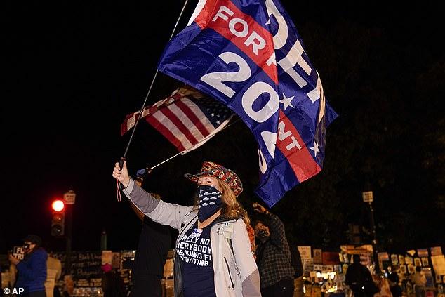 Jennifer Riggle, of Washington DC, waves flags in support of Democratic presidential candidate Joe Biden at Black Lives Matter Plaza